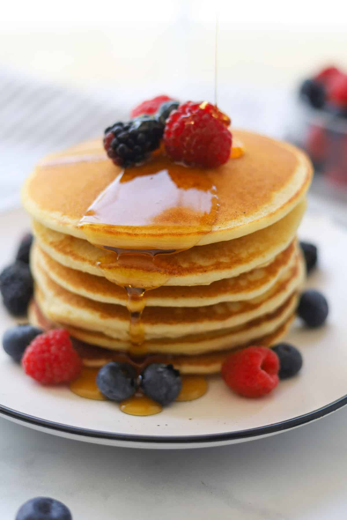 Stack of pancakes on a plate with drizzle of maple syrup.