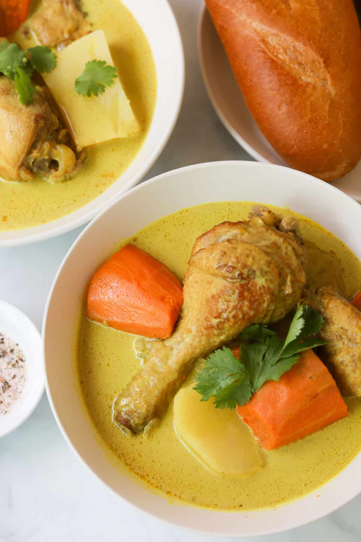 Yellow chicken curry with potatoes and carrots in a bowl.