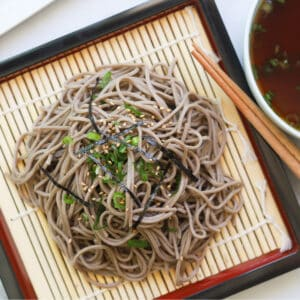 Buckwheat noodles garnished with seaweed strips and sesame seeds