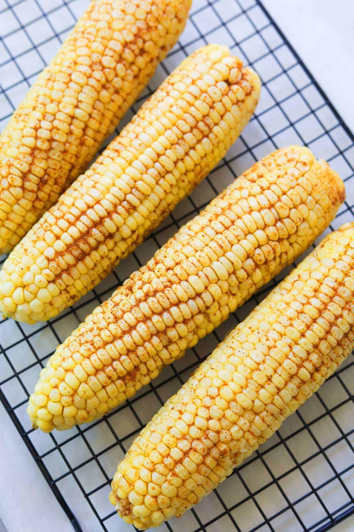 Four whole corn on a baking sheet.