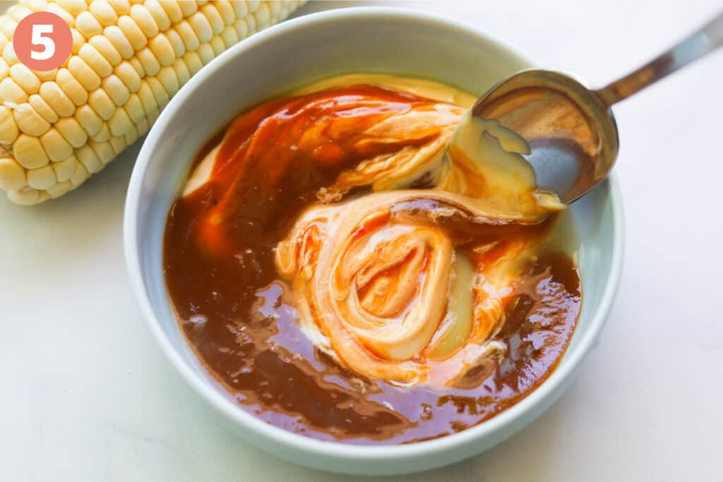 Mayo and bbq sauce mixed in a bowl.
