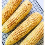 Corn on the cob on a baking sheet.