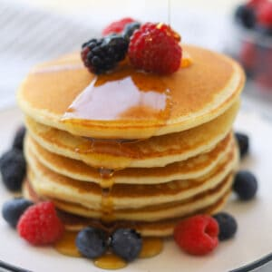 Stack of pancakes with syrup drizzle.