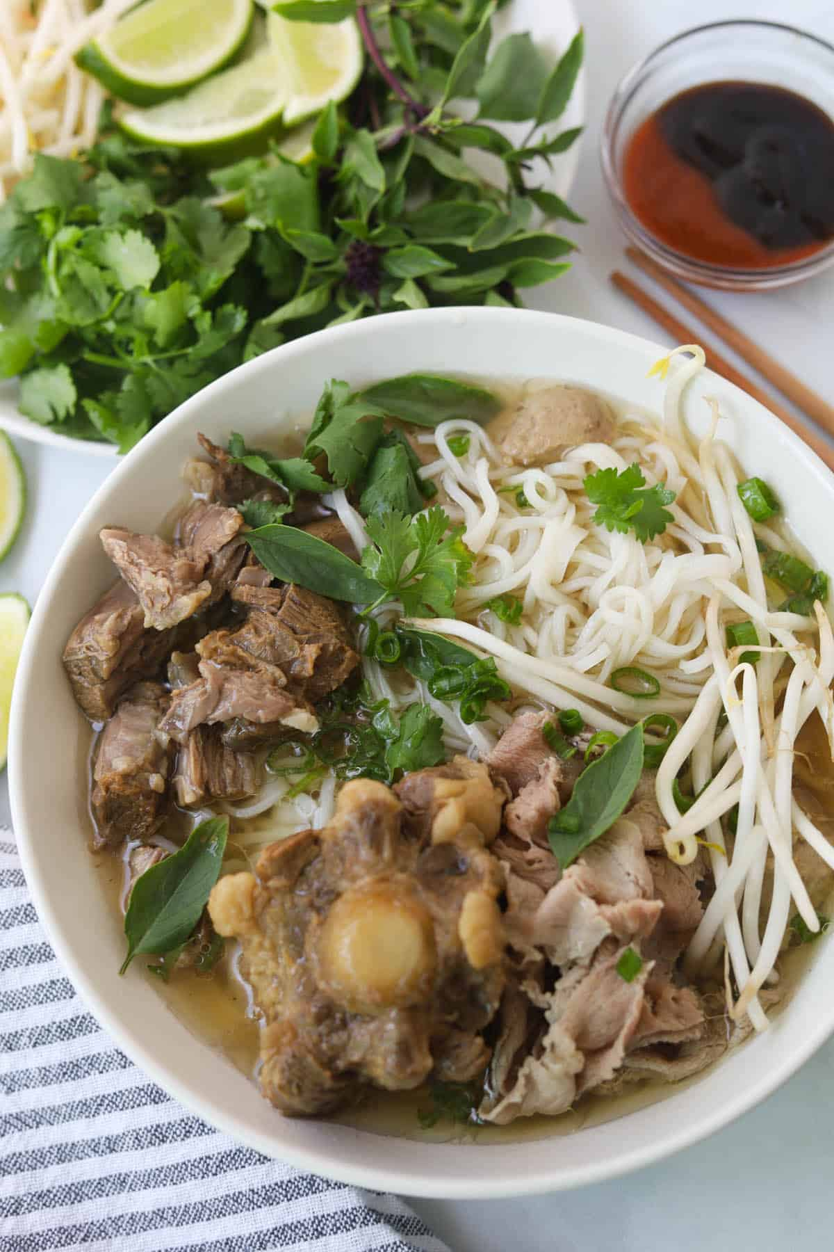 Bowl of rice noodle soup with beef and herbs.