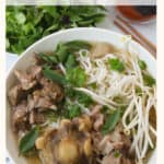 Bowl of rice noodle soup with meat and herbs.