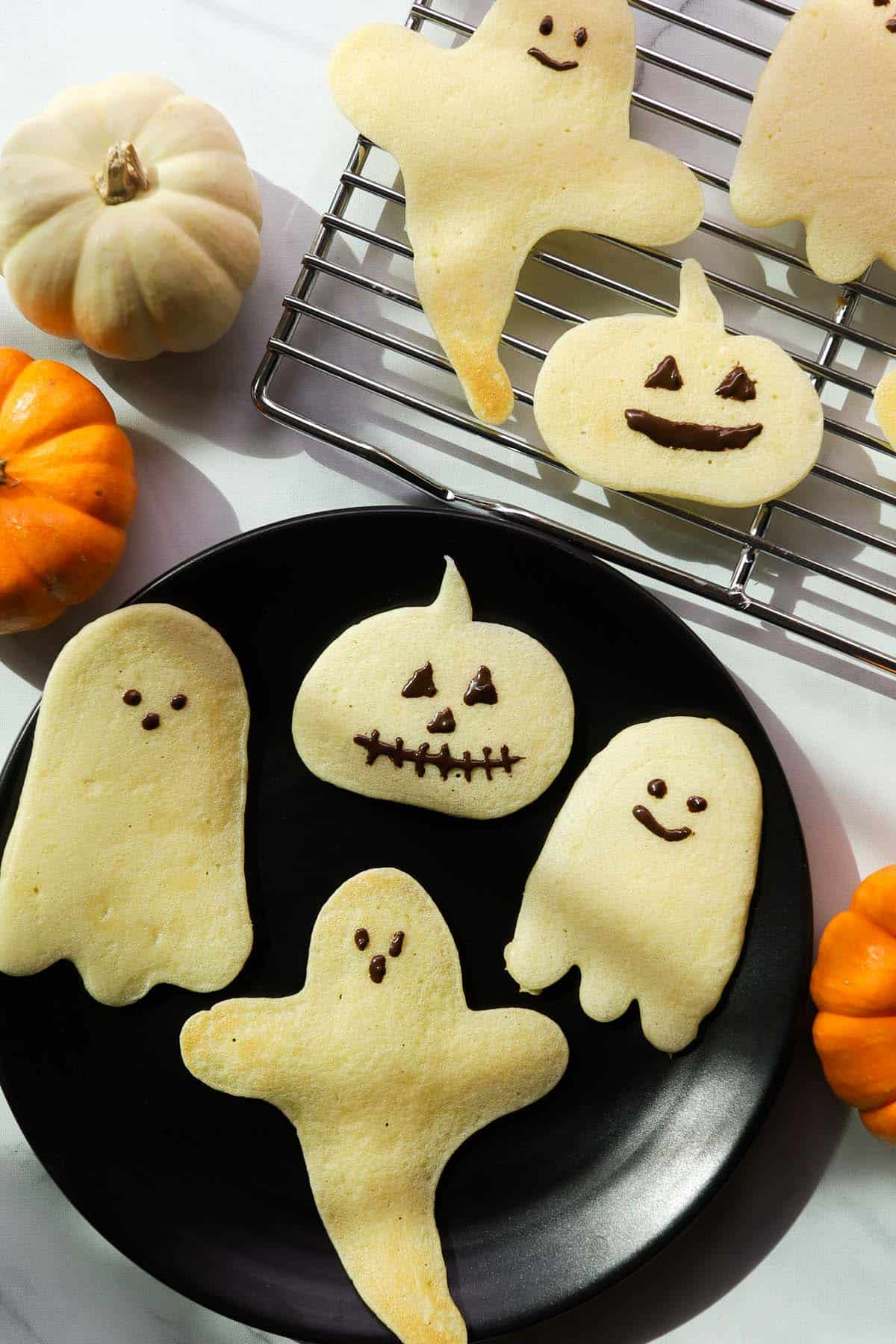 Pumpkin and ghost shaped pancakes on a plate.