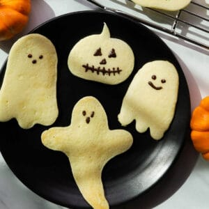 Ghost and pumpkin shaped pancakes on a plate.