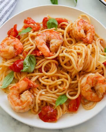 Shrimp cherry tomato pasta with basil on a plate.